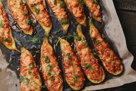 Baked stuffed zucchini boats. Zucchini stuffed with meat, vegetables, cheese and parsley. Healthy food concept. Zucchini boats in a baking tray on table. Top view.
