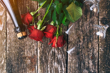 Valentines day card. Beautiful red roses. Flat lay composition. Bottle of champagne. Top view. Champagne glasses on wooden table. Romantic event. Valentines greeting card. Copy space. Rustic style 写真素材