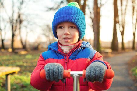 Portrait d'enfant mignon en plein air. Petit garçon en vêtements d'hiver jouant au parc. Heureux enfant marchant par temps froid. Enfance saine et heureuse. Mode enfant hiver et automne. Garçon drôle monter un scooter