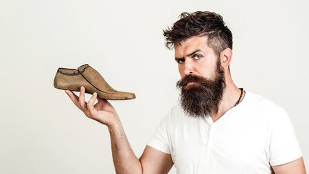 Handsome bearded shoemaker on white background. Bearded man holding last shoe. Looking at camera. Serious young cobbler sets up business. Shoemaker holding wooden footwear