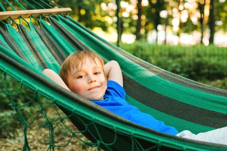 Happy child boy lying in a hammock in garden. Summer holidays concept. The child is resting in nature. Cute kid enjoy summer vacation with family at nature. Travel, vacation and lifestyle concept