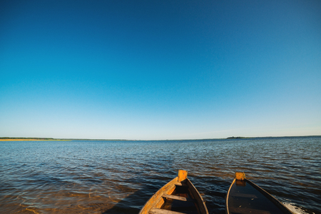 Wooden boats on the lake. Beautiful landscape. Summer vacation. Two boats on the lake against the blue sky