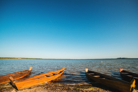 Wooden boats on the lake. Summer lake shore. Old fishing boats in sunny morning. Beautiful landscape