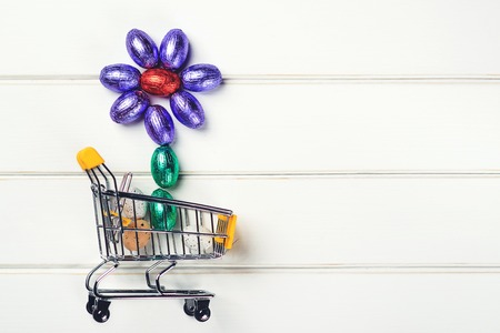 Easter eggs in small shopping cart. Happy Easter card. Easter shopping time. Sales, discounts and shop. Festive flower from small eggs. Easter Holidays. Copy space.