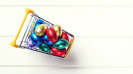 Mini shopping cart full of easter chocolate eggs. Happy Easter Holiday. Top view, copy space. Easter sales and discounts. Festive eggs wrapped in colored foil