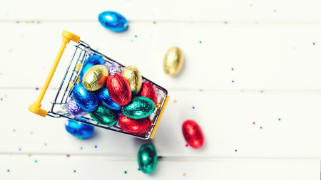 Easter shop background. Easter sales and discounts. Festive eggs wrapped in colored foil. Top view, copy space. Easter festive background. Happy Easter Holiday