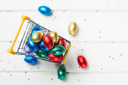 Color chocolate Easter eggs. Easter sales and discounts. Festive eggs wrapped in colored foil. Top view, copy space