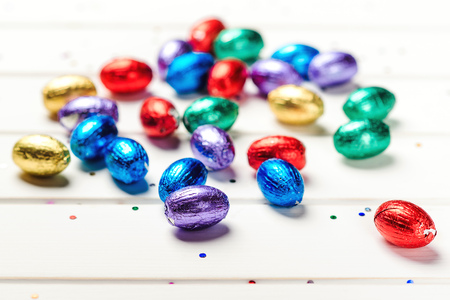 Easter background with small color eggs. Easter eggs on white wooden background. Mini eggs in color foil on table. Happy Easter Holiday.