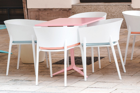 Empty coffee and restaurant terrace with pink table and white chairs. Cafe in the street. Summer terrace in Europe. Open air cafe. Modern cafe terrace outside