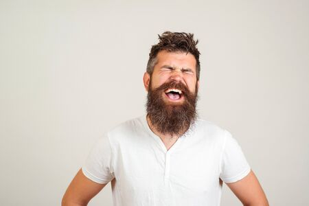 Stylish happy bearded man with closed eyes shouting on white background. Male excited face expression. Handsome bearded guy screaming