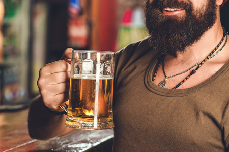 Cropped image of handsome bearded man is drinking beer in pub. Man enjoying good beer in night club. Party time, lifestyle, beer time Фото со стока