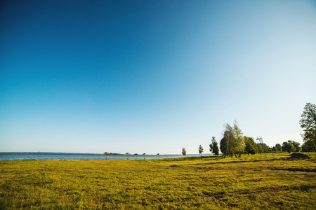 Blue sky and green trees over lake. Beautiful summer morning near lake. Water landscape. Summer vacation concept. Travel, lifestyle and nature concept
