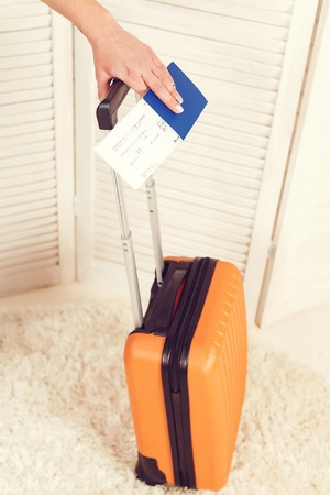 Close up woman hand holding passport and suitcase. Ready for trip. Traveler and lifestyle concept. Traveling abroad to travel on weekends. Passport and tickets in hand for flight airport