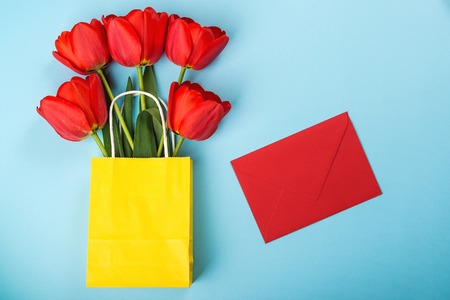 Red envelope and red tulips on blue fashion background. Mock up. Flat lay with copy space. Greeting card design with flowers. Spring tulips in yellow shopping bag