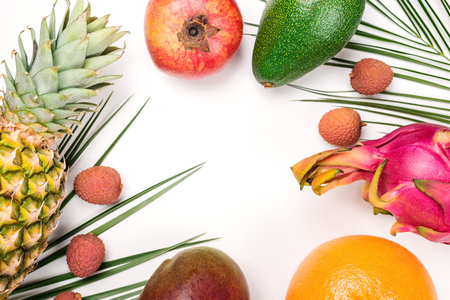 Creative summer tropical fruits composition. Green palm leaves and tropical fruits on white background. Summer concept. Flat lay, top view, copy space