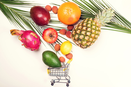 Shopping cart full of tropical fruit, space for text, banner. Health bio organic food concept. Creative flat lay composition from exotic fruits on white background. Fruits shop Фото со стока