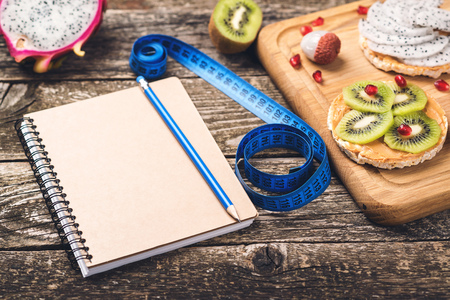 Toasts with fruit, measuring tape and empty notebook on wooden background. Slimming plan with fruits. Planning healthy diet concept. Healthy eating, dieting, slimming and weigh loss .