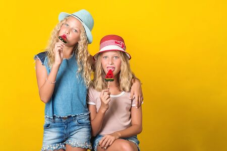 Happy twin sisters in summer hats. Teenagers girls posing on yellow background. Sisters in stylish summer outfit. Funny girls holding lolilops. Summer holidays concept. Copy space