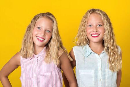 Happy smiling pretty teenage twins girls laughing with a perfect smile. People, emotions, teens and friendship concept. Cute sisters with blonde hair and amazing eyes on yellow wall Reklamní fotografie