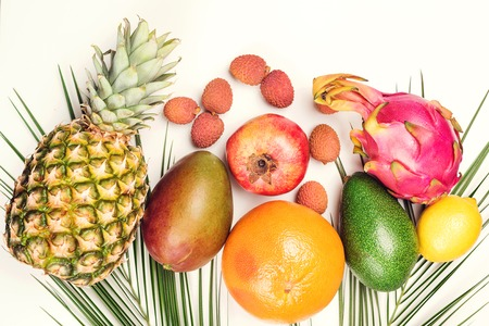Tropical fruits, palm leaves on white background. Healthy lifestyle and summer concept. Flat lay, top view. Pineapple, lychee, lemon, mango, avocado, kiwi and dragon fruit