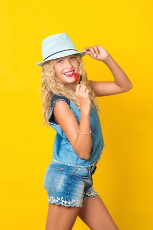 Teenager girl in summer hat posing on yellow background. Pretty girl with wavy blonde hair and perfect smile. Cheerful kid eating lollipop. Summer fashion