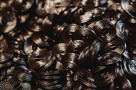 Dark jelly flavored licorice. Top view. Black candy spiral background. Candy shop. Street market. Handmade candies shop