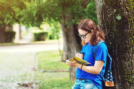 Pretty student girl in glasses, reads notebook, drinks coffee in campus park. Summer holidays, education, campus and teenage concept.