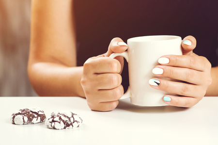 Cup of tea or coffee in female hands close up. Perfect woman manicure. Woman drinks tea, cookies on table. White cup in womens hands with perfect manicure Фото со стока