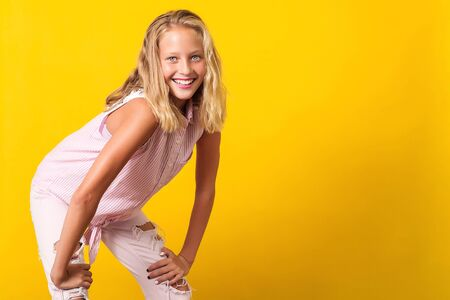 Cute pre-teen girl wearing fashion summer clothes posing on yellow background. 10 years old girl with beauty eyes, blonde hairl and white teeth smile. Kid urban style, pre teen summer fashion