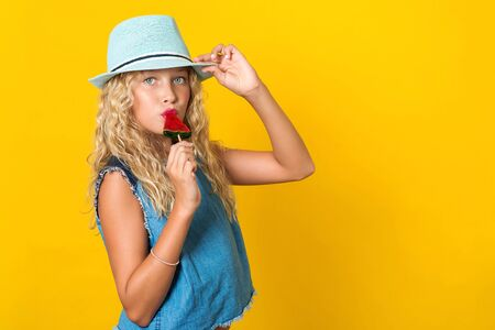 Fashionable teenage girl in summer hat on yellow background. Summer holidays concept. Beautiful girl with wavy blonde hair and perfect smile. Girl eating summer lollipop. Copy space