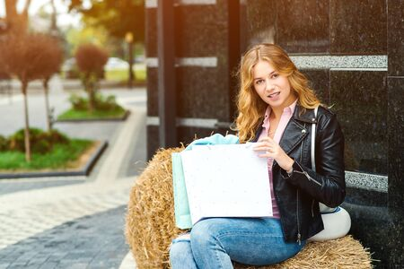 Happy fashionable woman with shopping bags outdoors. People, fashion, lifestyle concept. Positive emotions. Girl enjoying purchases. Seasonal sales concept