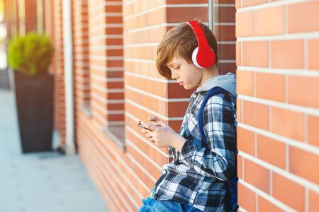 Stylish kid boy with headphones using phone at city street. Young boy plays online game at smartphone. Preteen boy listens to the music on smart phone.