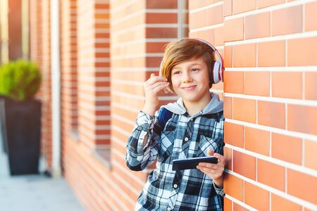 Pre-teenage boy with headphones and mobile phone listening to music at city street. Fashion boy hairstyle. Popular lifestyle music play list. Fashion kid urban style