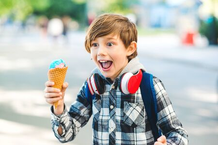 Happy kid eating ice cream at the city centre. Stylish boy 8 years old walking on street. Emotional child holding ice cream Banque d'images