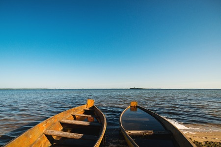 Old wooden rowing boats in sunny summer morning. Summer lake shore. Old fishing boats on the lake Фото со стока