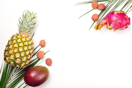 Exotic fruits on a white background, copy space. Pineapple, mango, dragon fruit, lychee. Top view of tropical fruits. Healthy food concept. Fresh fruit flat lay. Mockup