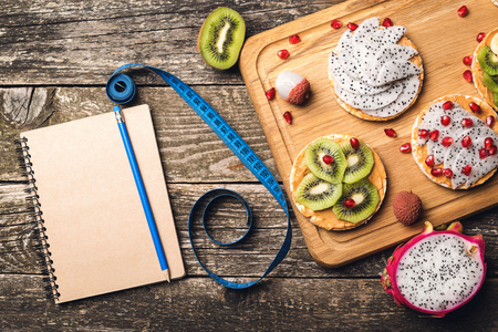 Planning healthy diet concept. Workout and fitness dieting. Fruits toasts, measuring tape and empty notebook on wooden background. Slimming plan with fruits. Top view, copy space.