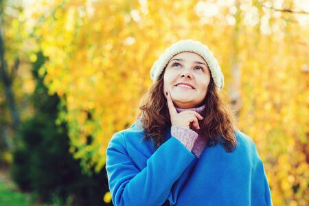 Cheerful young woman wearing warm coat and knitted hat. Autumn women fashion, copy space. Girl walking in autumn park. Emotional woman thinking and smiling Banque d'images
