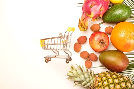 Exotic tropical fruits background and mini shopping cart. Flat lay composition, space for text, banner. Fruits eco shop. Health bio organic food concept