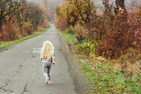 Happy little girl with blonde long hair running away on the road, back view. Walk in autumn time. Stylish fashion child outdoors. Autumn holidays concept. Childhood, leisure and people