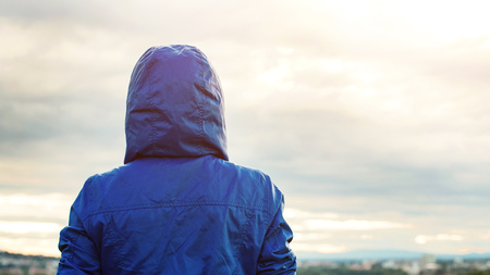 Back view of athlete woman looking sunset over city skyline after exercising. Motivation, sport and fitness lifestyle concept. Female tourist person in hooded jacket outdoors. Фото со стока