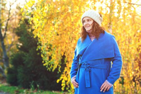 Beautiful autumn woman outdoors. Woman fashion. Young woman dressed in blue coat and warm hat, walking in autumn park. Beautiful girl on fall nature background. People, lifestyle and autumn concept