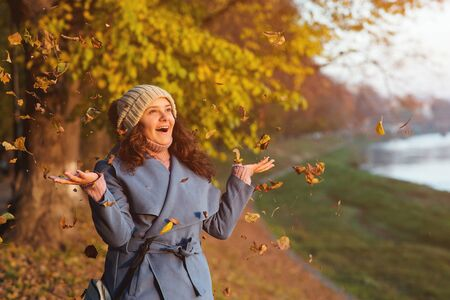 Happy autumn woman portrait. Young woman throws autumn leaves at park. Beautiful girl in blue coat enjoys autumn weather. Woman fashion. Autumn leaves