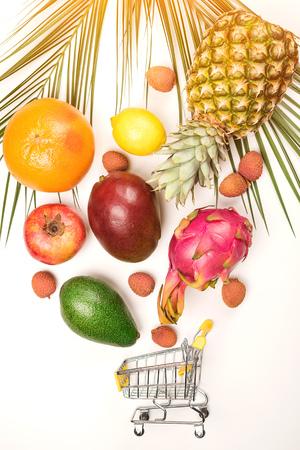 Organic fruits falling into mini shopping cart. Organic market concept. Exotic tropical fruits on white background. Grocery shopping cart Фото со стока