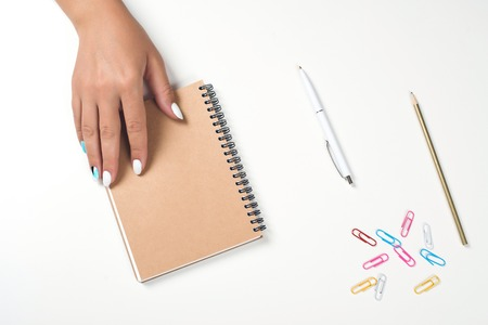 Female hand writing in a notebook at the desk. Top view, copy space. White table with planning book. Womans hands with perfect manicure. Mockup for your design. Flat lay style