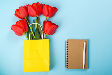 Spring tulips, notebook, pen on blue background. Flat lay with copy space. Red tulips in yellow shopping bag. Empty notebook for planning day. Spring card with flower.