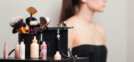 Professional makeup brushes and tools. Fashion, beauty, and cosmetics. Set of brushes on blurred background, with copy space. Makeup artist workplace. Modern airbrush, mockup.