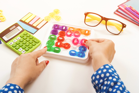 Woman playing game at work desk. The concept of concentration, logical thinking. Workplace table with calculator, pens, female glasses and notebooks. Modern logic games