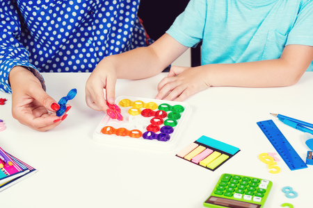 Mother and kid plays logic game at table. Logical thinking training. Modern logic games. Workplace table with calculator, pens and notebooks. Education and development concept.