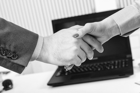 Businesswoman and businessman shaking hands, close-up. Business partnership. Greet or thanks gesture, product advertisement. Strike a bargain or deal concept. Фото со стока